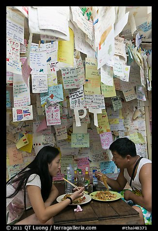 Couple eating Pad Thai below notes of praise left by customers, Ko Phi Phi. Krabi Province, Thailand (color)