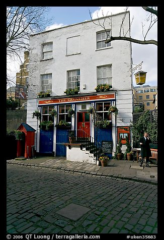 Cobblestone mews, pub, and man standing outside. London, England, United Kingdom (color)