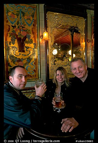 Friends cheering up with a beer in front of echted glass and fine tiles of pub Princess Louise. London, England, United Kingdom (color)