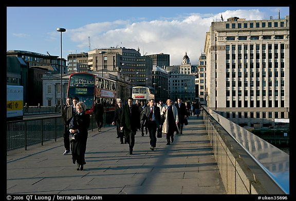 Office workers pouring out of the city of London across London Bridge, late afternoon. London, England, United Kingdom (color)