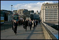 Office workers pouring out of the city of London across London Bridge, late afternoon. London, England, United Kingdom ( color)