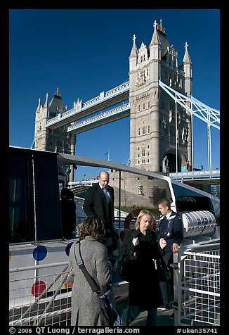 Passengers disembarking a boat in their morning commute, Tower Bridge in the background. London, England, United Kingdom