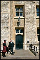 Yeoman Warder talking with man in suit in front of the Jewel House, Tower of London. London, England, United Kingdom