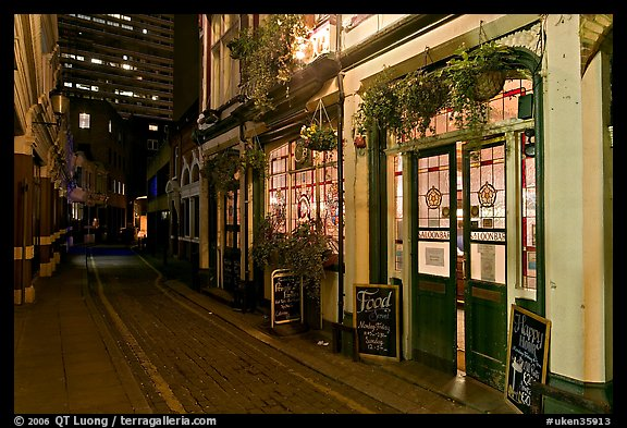 Saloon bar and cobblestone alley at night. London, England, United Kingdom (color)