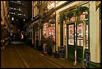 Saloon bar and cobblestone alley at night. London, England, United Kingdom