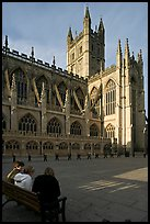 Young people sitting on a bench in a square below Bath Abbey. Bath, Somerset, England, United Kingdom