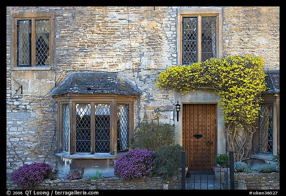 Stone house facade with flowers, Castle Combe. Wiltshire, England, United Kingdom (color)