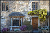 Stone house facade with flowers, Castle Combe. Wiltshire, England, United Kingdom