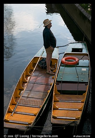 Man standing in a rowboat, old town moat. Canterbury,  Kent, England, United Kingdom