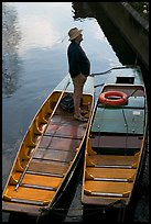 Man standing in a rowboat, old town moat. Canterbury,  Kent, England, United Kingdom (color)