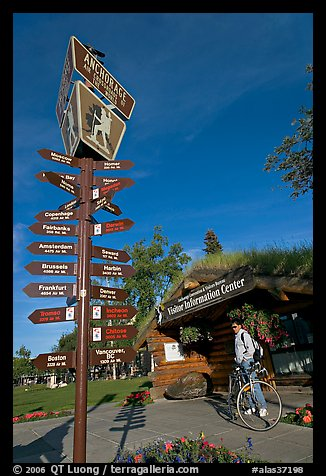 Sign Air Crossroads of the World, man on bicycle in front of visitor center. Anchorage, Alaska, USA (color)