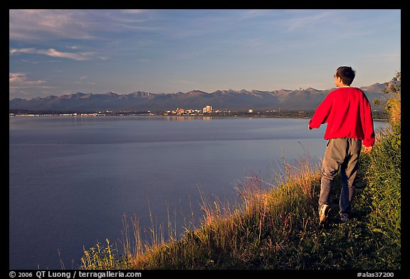 Man walking on the edge of Knik Arm in Earthquake Park, sunset. Anchorage, Alaska, USA (color)
