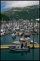 Small boat loaded at pier, harbor, and mountains. Whittier, Alaska, USA (color)