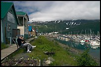 Couple sitting on bench by the harbor. Whittier, Alaska, USA (color)