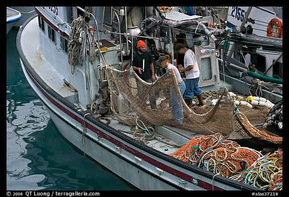 Fishermen repairing nets on fishing boat. Whittier, Alaska, USA