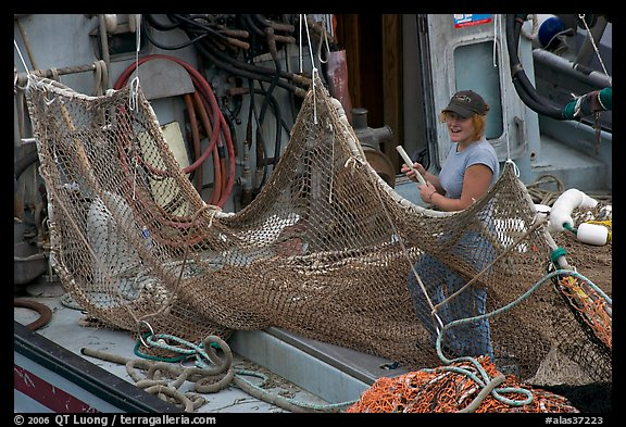 Woman repairing net on fishing boat. Whittier, Alaska, USA (color)
