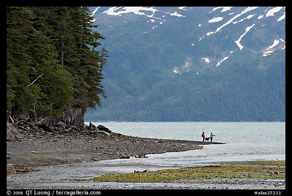 Women fishing and dog, at the edge of Passage Canal Fjord. Whittier, Alaska, USA (color)
