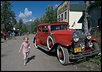 Girl on main street with red classic car. McCarthy, Alaska, USA