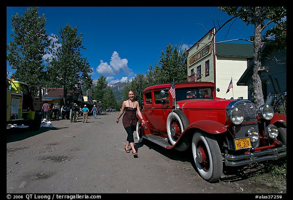 Woman walking next to red classic car. McCarthy, Alaska, USA (color)