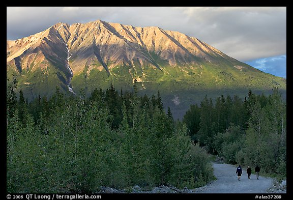 People strolling on unpaved road at sunset. McCarthy, Alaska, USA (color)