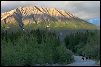 People strolling on unpaved road at sunset. McCarthy, Alaska, USA