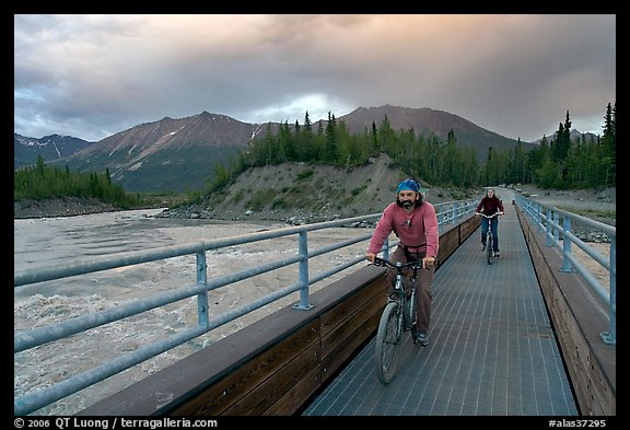 Mountain bikers crossing Kennicott River Footbridge at sunset. McCarthy, Alaska, USA