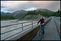 Woman on mountain bike crossing the footbridge. McCarthy, Alaska, USA (color)