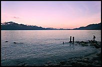 Boy standing in front of Resurrection Bay, sunset. Seward, Alaska, USA (color)