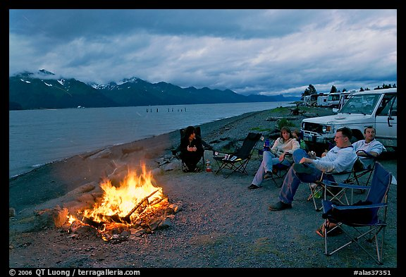 Sitting by campfire at midnight, waterfront campground. Seward, Alaska, USA