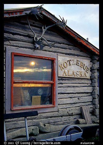 Log cabin with caribou antlers and sun reflected in window. Kotzebue, North Western Alaska, USA (color)