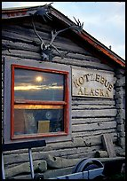 Log cabin with caribou antlers and sun reflected in window. Kotzebue, North Western Alaska, USA