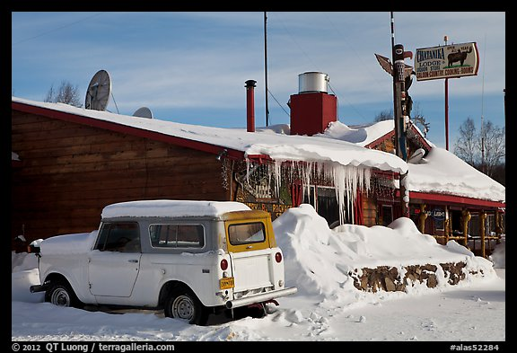 Old truck parked next to lodge in winter. Alaska, USA (color)