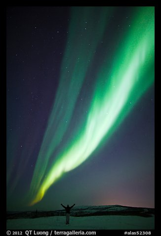 Aurora Borealis streaming above person with outstretched arms. Alaska, USA