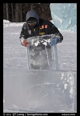 Ice carver lifting ice block. Fairbanks, Alaska, USA (color)