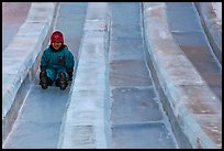 Girl on slide made of ice, George Horner Ice Park. Fairbanks, Alaska, USA (color)