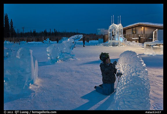 Child amongst ice sculptures at dusk. Fairbanks, Alaska, USA (color)