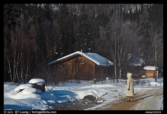 Woman with winter coat walking on path to cabins. Chena Hot Springs, Alaska, USA
