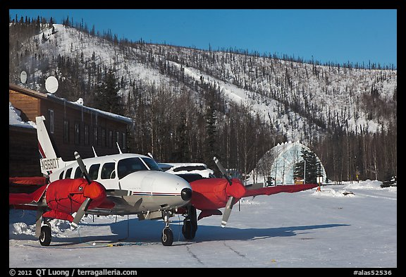 Plane with engine block warmers on frozen runway. Chena Hot Springs, Alaska, USA (color)