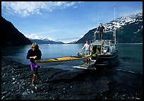 Man and woman carry kayak out of small boat at Black Sand Beach. Prince William Sound, Alaska, USA ( color)