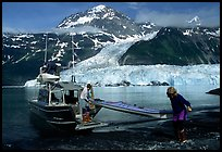 Man and woman  unload  kayak from the water taxi boat at Black Sand Beach. Prince William Sound, Alaska, USA (color)