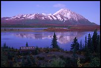 Mountains and lake at dusk, cabin with Denali sign. Alaska, USA