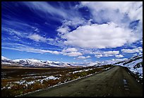 Denali Highway under large white clouds. Alaska, USA