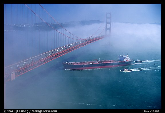 Tanker ship cruising under the Golden Gate Bridge in the fog. San Francisco, California, USA