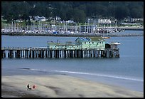 Couple on the beach and pier, Pillar Point Harbor. Half Moon Bay, California, USA (color)