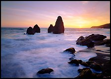 Wave action, seastacks and rocks with sun setting, Rodeo Beach. California, USA