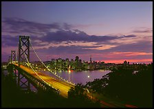 Bay Bridge and city skyline with lights at sunset. San Francisco, California, USA