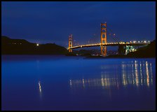 Golden Gate Bridge reflected in wet sand, blue hour. San Francisco, California, USA