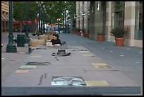 Woman sitting at a commemorative table in a downtown alley. San Jose, California, USA