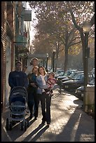 Family strolls on the sidewalk of University Avenue. Palo Alto,  California, USA (color)