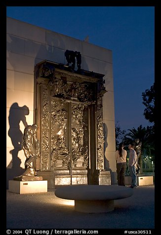A couple contemplates Rodin's Gates of Hell at night. Stanford University, California, USA (color)